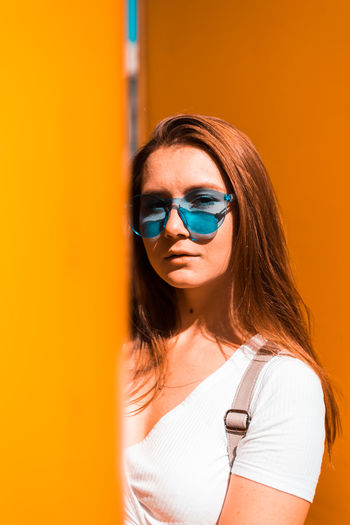 Portrait of beautiful woman standing against orange wall