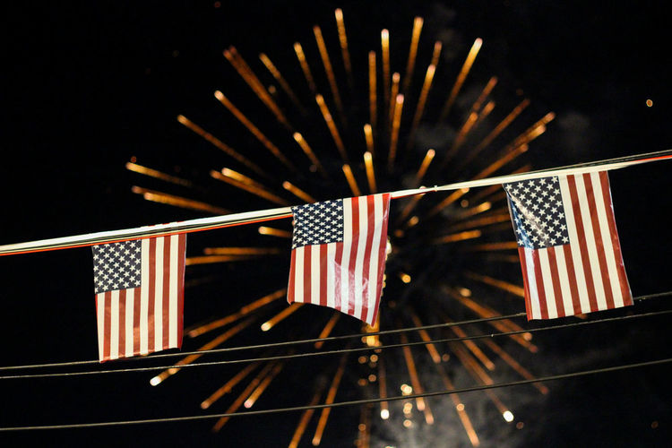 Low angle view of american flags against illuminated fireworks at night