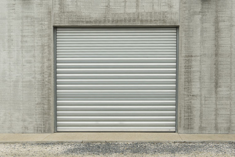 Closed metallic garage door in a grey industial wall Garage Door Garage Door Gray Industrial Closed Architecture Building Exterior Entrance Protection No People Security Shutter Built Structure Metal Outdoors Steel