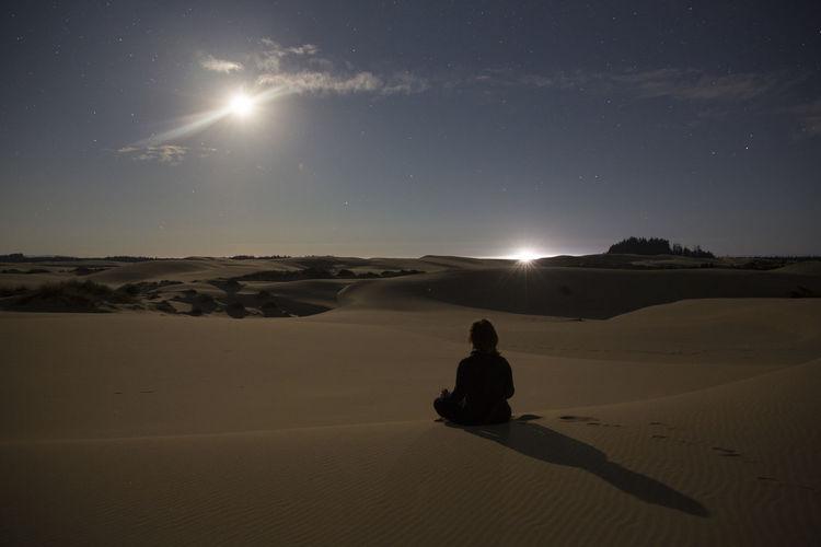 Rear view of man on desert against sky