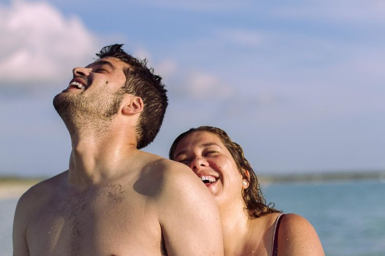 Portrait of a smiling young couple against sky