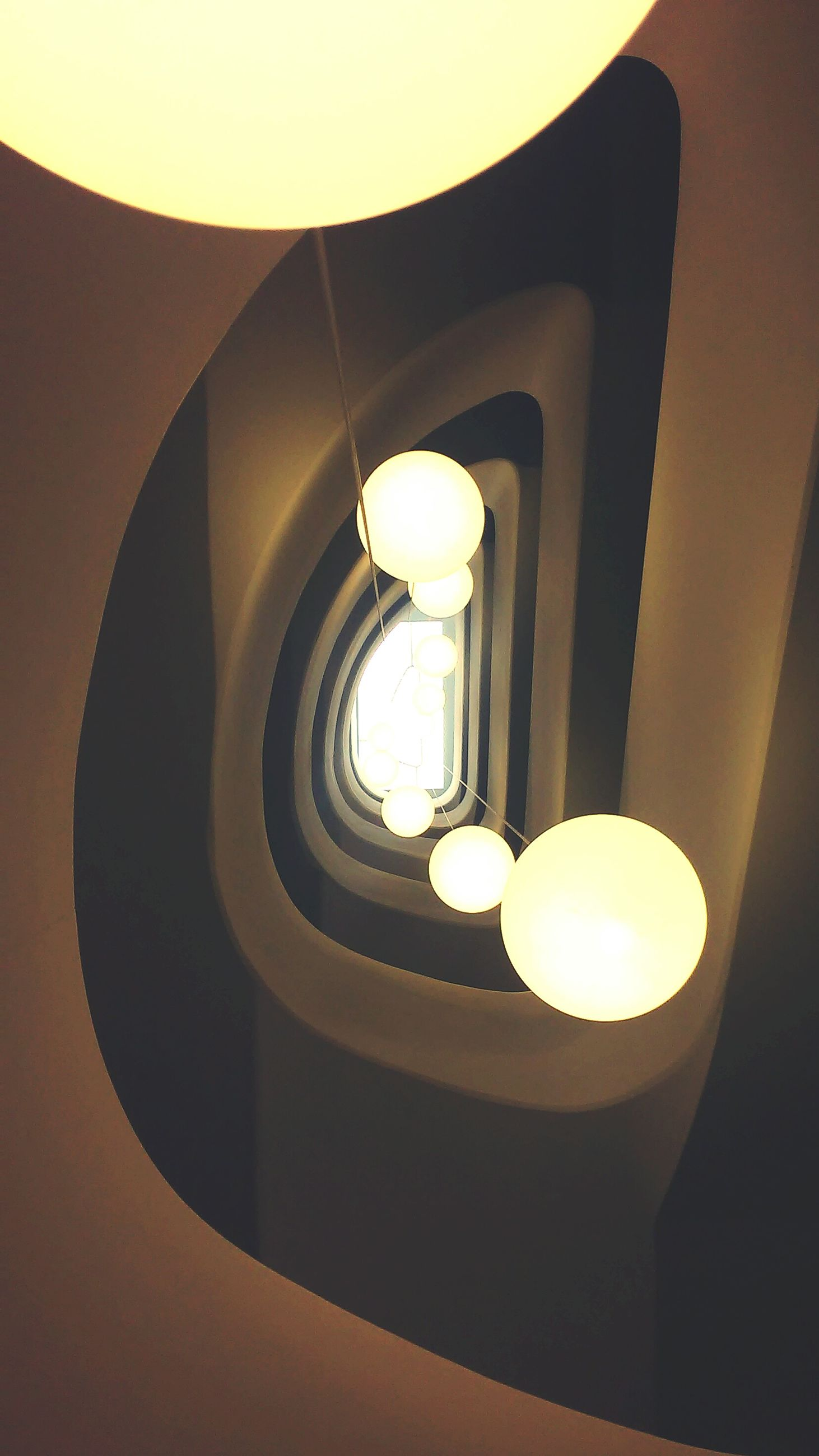 illuminated, low angle view, lighting equipment, architecture, built structure, indoors, electricity, electric light, ceiling, electric lamp, glowing, lamp, directly below, no people, building exterior, light - natural phenomenon, light bulb, hanging, wall - building feature, circle