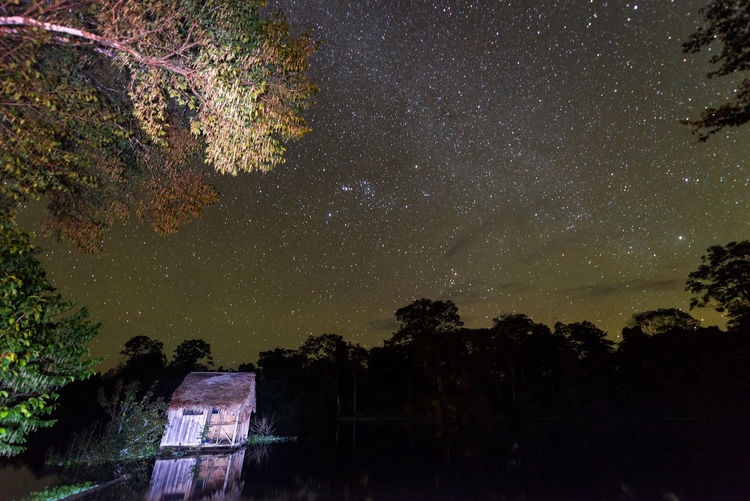 Stars over the Amazon Rainforest with a small shack in the foreground near Iquitos, Peru Adventure Amazon Amazonas Amazonia Bungalows Forest Green Hut Iquitos  Iquitos, Perú Jungle Lake Lodge Nature Outdoors Park Peru Rainforest Reflection River Scenics South America Tree Tropical Vacation