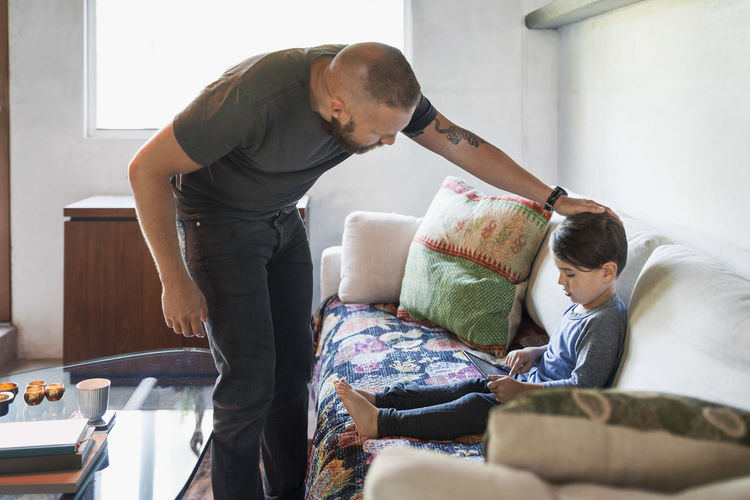 Father looking at son using digital tablet on sofa at home