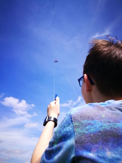 Low angle view of boy flying kite against blue sky during sunny day