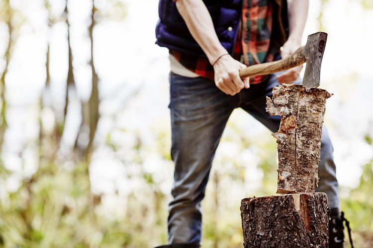Midsection of man holding tree trunk