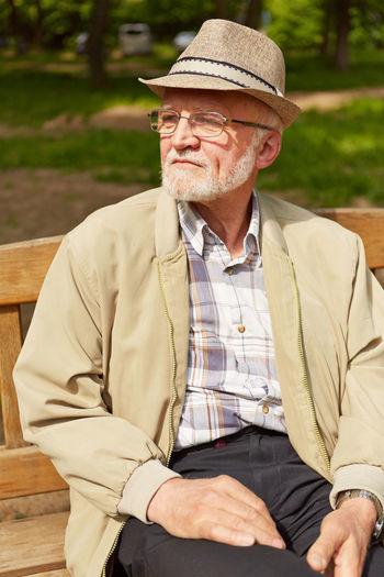 Senior Man Wearing Hat Sitting At Park