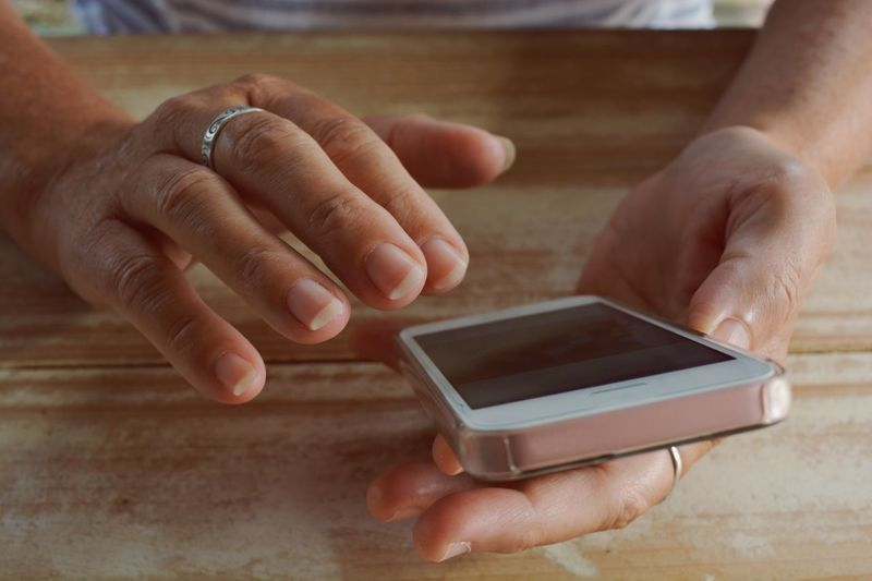 Close-up of man using mobile phone on table