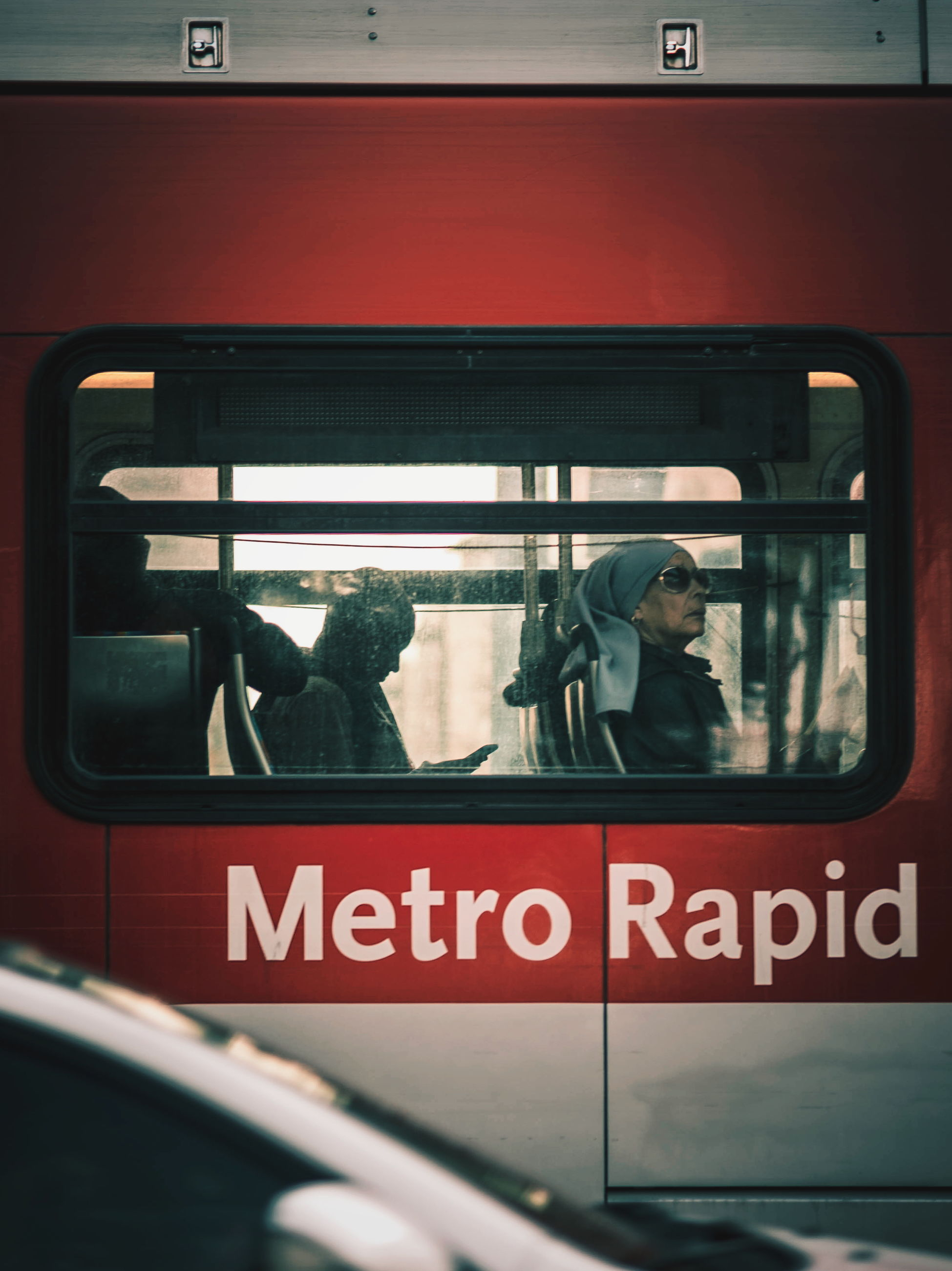 transportation, public transportation, mode of transport, text, window, train - vehicle, real people, day, land vehicle, men, communication, red, bus, women, sitting, lifestyles, vehicle seat, indoors, one person, people