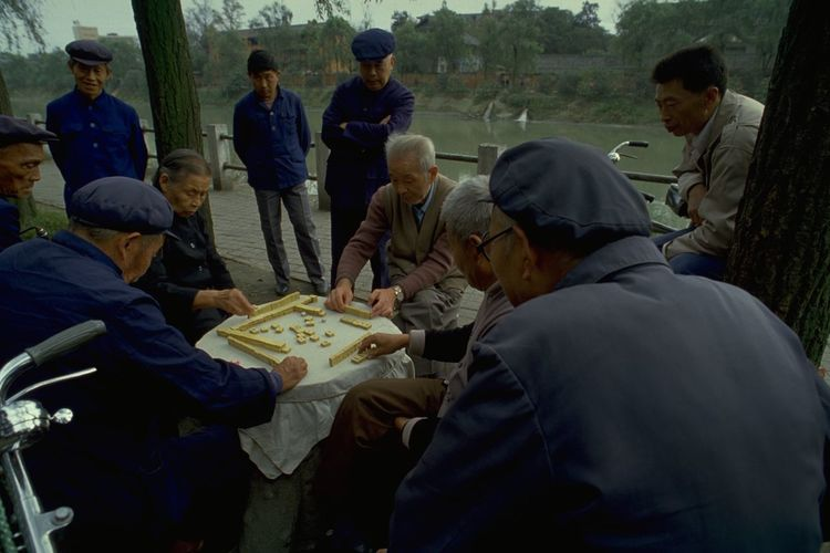 Mahjong In Guangzhou Old People in Mao Suits Playing Mahjong in Guangzhou, China. Commonly played by four players, Mahjong originated in China during the Qing dynasty. The game is played with a set of 144 tiles, based on Chinese characters and symbols. Each player is given 13 tiles at the start, taking it in turns to draw and discard a fourteenth tile to try and make a winning hand of four melds (three identical tiles) and an eye (a pair of identical tiles). Of course, Mahjong is a little more complicated than that, but it was interesting to watch these Chinese players continue an age-old tradition; when on a photo walkabout in Guangzhou, China. Open-air games often attract a little crowd of onlookers, and the occasional foreign tourist posing as a travel photographer. What made this picture special for me was the captivating look on these old Chinese faces; and their clothing. These dark blue tunics were originally known as the Zhongshan suit, after Sun Yat-sen (also called Sun Zhongshan) helped revolutionise China and overthrow the the Qing (or Manchu) dynasty in the early 20th century. Sometimes called the 'father of modern China', Zhongshan is credited with giving the suit its symbolisms. The four pockets on the front represent the Four Virtues: politeness, justice, honesty, and a sense of shame. The five buttons on the front then represent the five branches of government in the constitution of the Republic of China. The three buttons on the cuff represent Sun's Three Principles of the People: nationalism, democracy, and people's livelihood. The 'blue look' was later made famous by Mao Zedong and the tunic subsequently became known as a 'Mao suit'. http://pics.travelnotes.org/ ASIA Authentic Blue Caps China Green Guangzhou Landscape Local Mahjong Mao Suits Maximum Closeness Michel Guntern Old Lady Old Men People People Watching Real People Riverside Table Games Travel Travel Photography Travel Photos Travel Pics Let's Go. Together. My Best Photo
