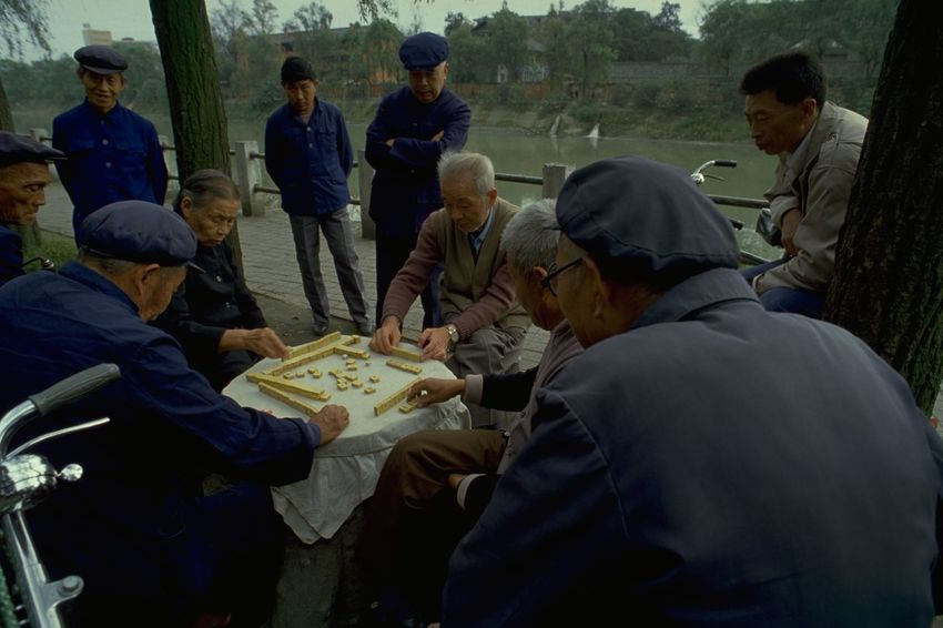 Mahjong In Guangzhou Old People in Mao Suits Playing Mahjong in Guangzhou, China. Commonly played by four players, Mahjong originated in China during the Qing dynasty. The game is played with a set of 144 tiles, based on Chinese characters and symbols. Each player is given 13 tiles at the start, taking it in turns to draw and discard a fourteenth tile to try and make a winning hand of four melds (three identical tiles) and an eye (a pair of identical tiles). Of course, Mahjong is a little more complicated than that, but it was interesting to watch these Chinese players continue an age-old tradition; when on a photo walkabout in Guangzhou, China. Open-air games often attract a little crowd of onlookers, and the occasional foreign tourist posing as a travel photographer. What made this picture special for me was the captivating look on these old Chinese faces; and their clothing. These dark blue tunics were originally known as the Zhongshan suit, after Sun Yat-sen (also called Sun Zhongshan) helped revolutionise China and overthrow the the Qing (or Manchu) dynasty in the early 20th century. Sometimes called the 'father of modern China', Zhongshan is credited with giving the suit its symbolisms. The four pockets on the front represent the Four Virtues: politeness, justice, honesty, and a sense of shame. The five buttons on the front then represent the five branches of government in the constitution of the Republic of China. The three buttons on the cuff represent Sun's Three Principles of the People: nationalism, democracy, and people's livelihood. The 'blue look' was later made famous by Mao Zedong and the tunic subsequently became known as a 'Mao suit'. http://pics.travelnotes.org/ ASIA Authentic Blue Caps China Green Guangzhou Landscape Local Mahjong Mao Suits Maximum Closeness Michel Guntern Old Lady Old Men People People Watching Real People Riverside Table Games Travel Travel Photography Travel Photos Travel Pics Let's Go. Together.