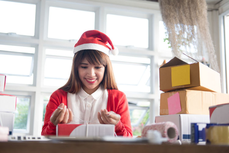 Smiling young woman wearing santa hat working at office
