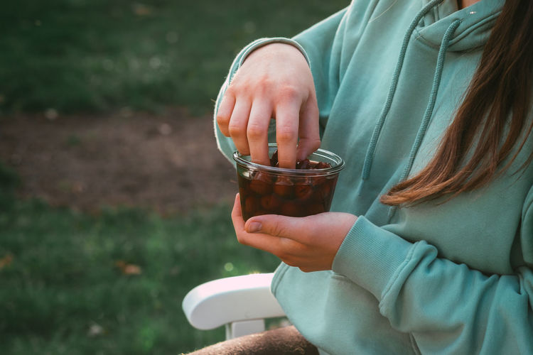 Midsection of woman holding berries in container