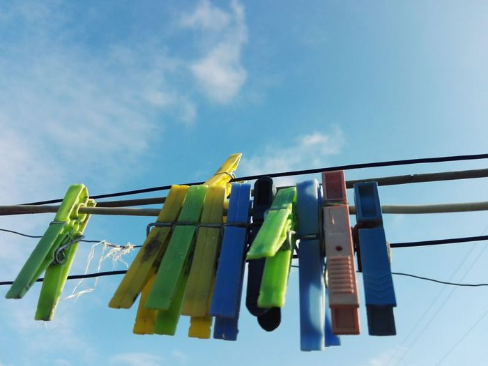 Low angle view of clothespins hanging on clothesline