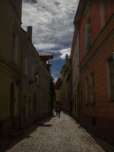 Alley Architecture Building Building Exterior Built Structure City Cloud - Sky Diminishing Perspective Direction Incidental People Leisure Activity Lifestyles Nature One Person Outdoors Real People Residential District Sky Street The Way Forward Walking