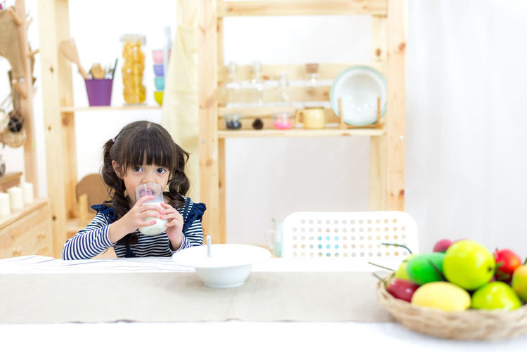 Portrait of boy holding ice cream at home