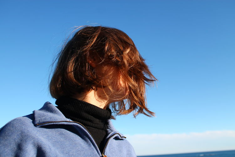 Woman with tousled hair against blue sky