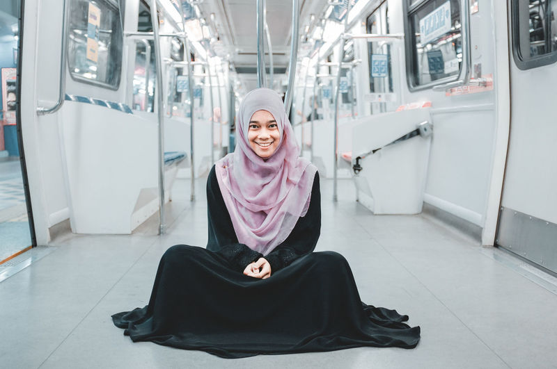 Woman In Hijab Smiling One Person Hijab Looking At Camera Portrait Happiness Headscarf Full Length Women Front View Sitting Lifestyles Emotion Beautiful Woman Indoors  Fashion Train Commuter Train Travel City Empty Train International Women's Day 2019