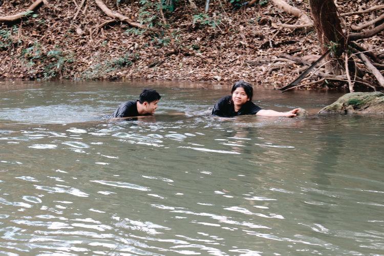 Portrait of friends sitting in water