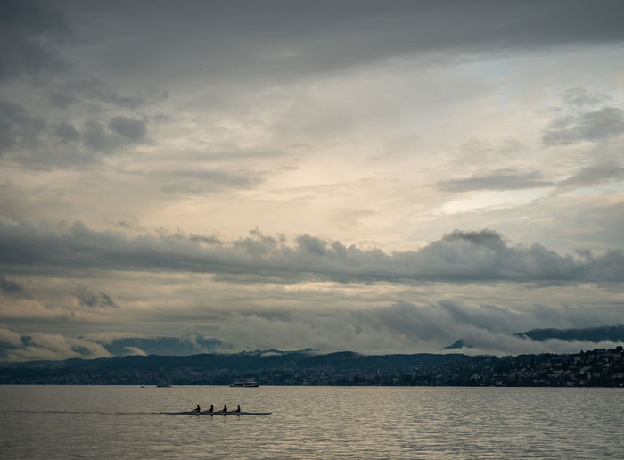 Distant view of people sculling in lake against cloudy sky