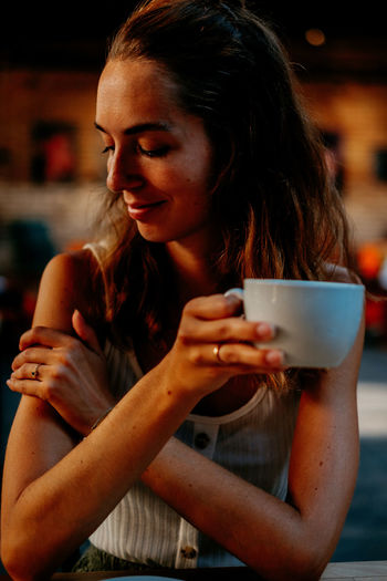 Close-up of woman drinking coffee in cafe