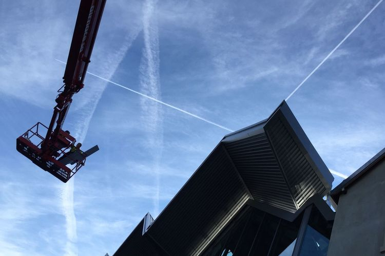 Low angle view of cherry picker and building against sky