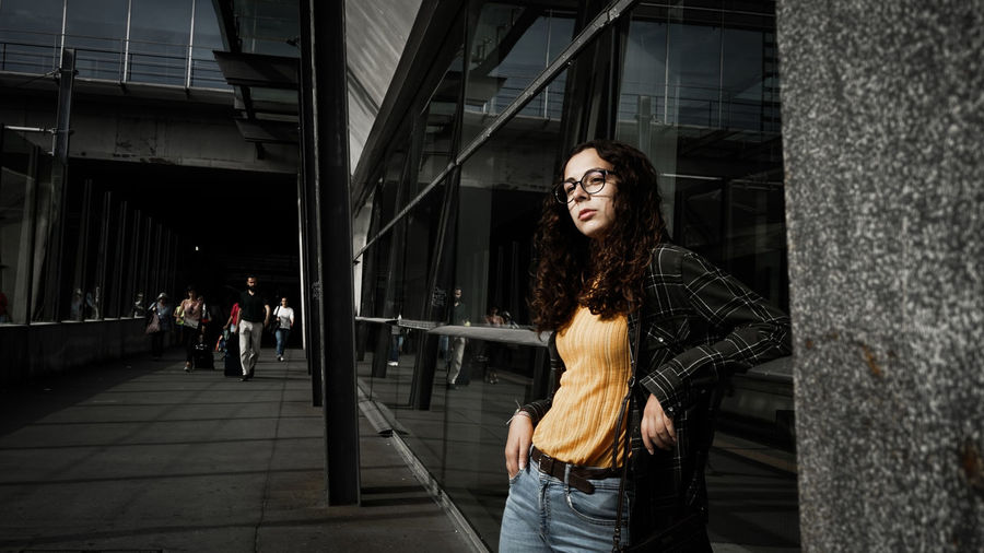 Thoughtful young woman standing outside building