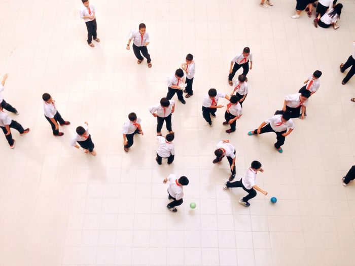 High angle view of students playing on tiled floor