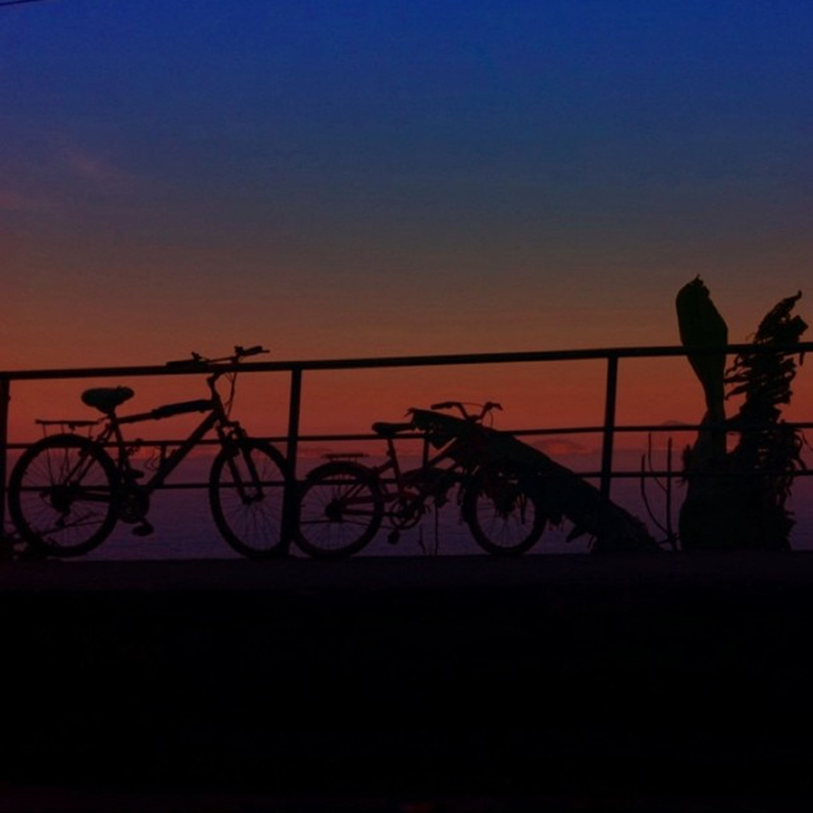 sunset, silhouette, sky, bicycle, orange color, copy space, transportation, dusk, outdoors, clear sky, mode of transport, nature, no people, railing, blue, low angle view, land vehicle, creativity, tranquility, art