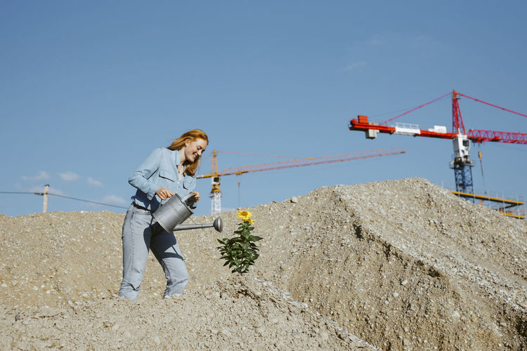 Woman standing on construction site against clear sky