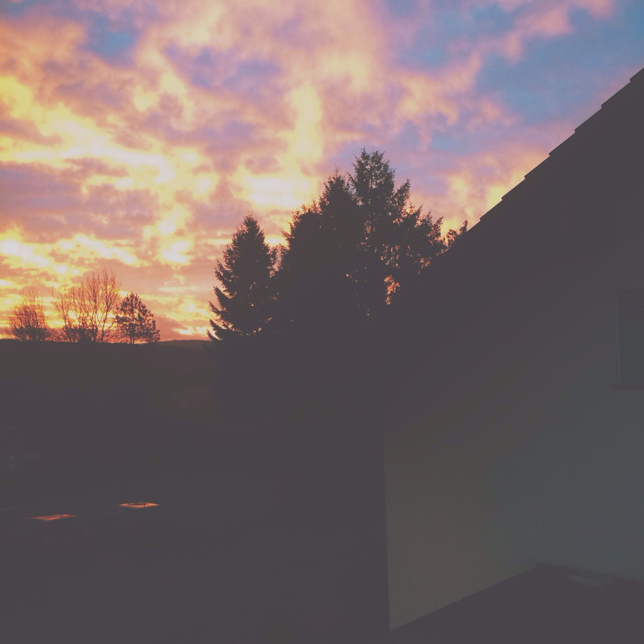 sunset, silhouette, sky, architecture, built structure, building exterior, tree, orange color, cloud - sky, house, nature, beauty in nature, low angle view, cloud, dusk, residential structure, outdoors, tranquility, scenics, no people