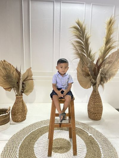 Cute boy sitting by palm tree