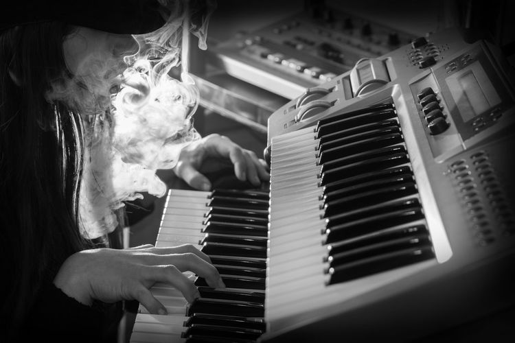 Close-up of woman exhaling smoke while playing piano