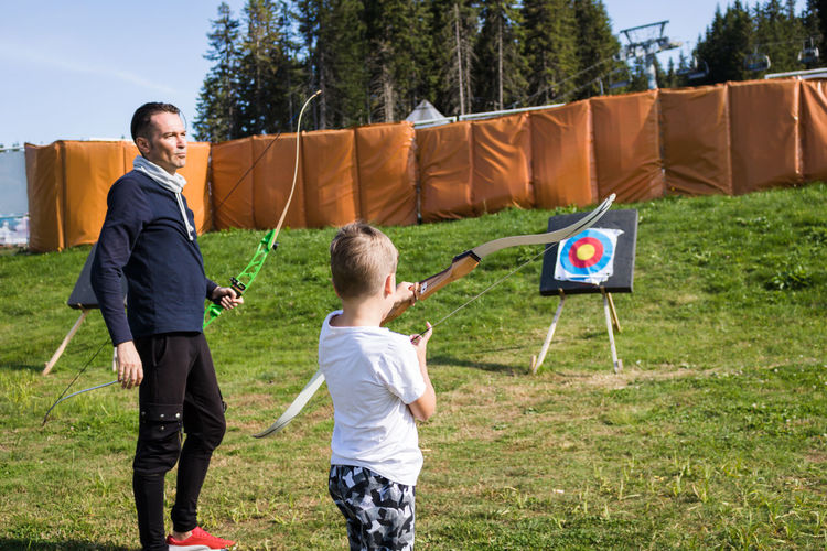 Coach giving archery training to boy outdoor