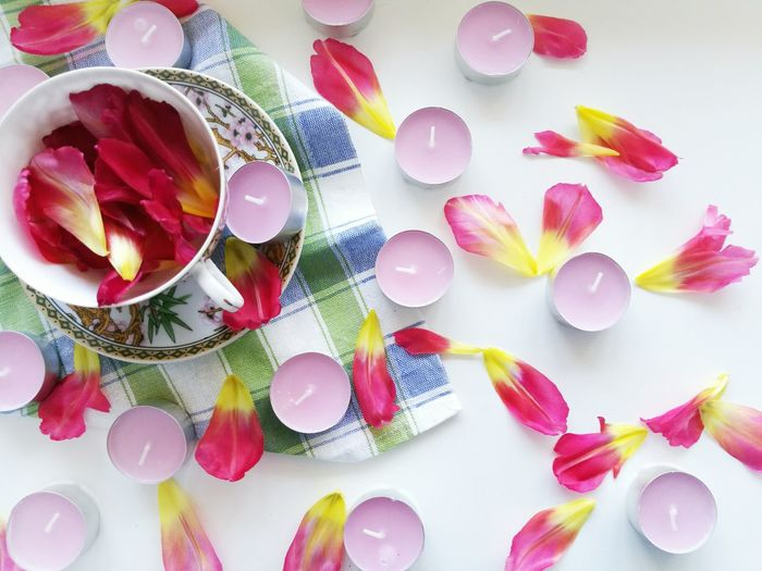 High angle view of petals and candles on white background