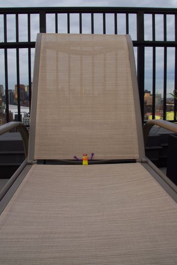 Middle finger puppet chillin'.... Toy Humor Way Up Here Sky Chaise Lounge Chillin' Waiting For Sunset Fence Citylife NYC Photography