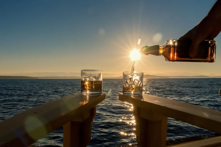 Pouring whiskey alcohol into rocks glasses by the sea at sunset. Adirondack Chairs Cruise Ship Glasses Pouring Beach Beauty In Nature Close-up Day Deck Drink Drinking Glass Horizon Over Water Nature Outdoors Refreshment Rocks Sailing Scenics Sea Sky Sun Sunlight Sunset Water Whiskey