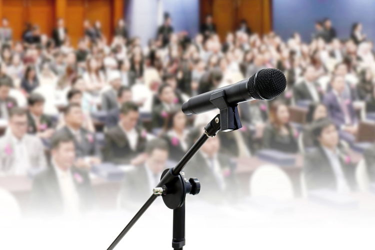 Close-up of microphone with people in background at conference