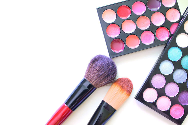 Close-up of eyeshadows with make-up brushes on table