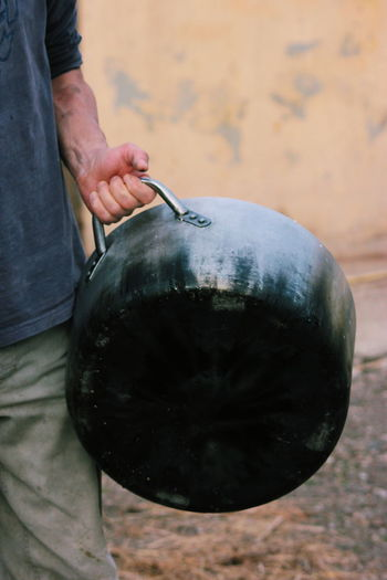 Midsection of man holding kitchen utensil outdoors