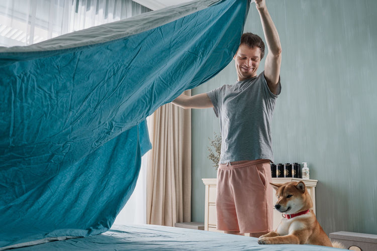 Young man and his funny dog are putting the bedding cover or mattress pad on the bed
