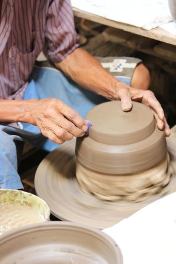 Midsection of man molding shape on pottery wheel