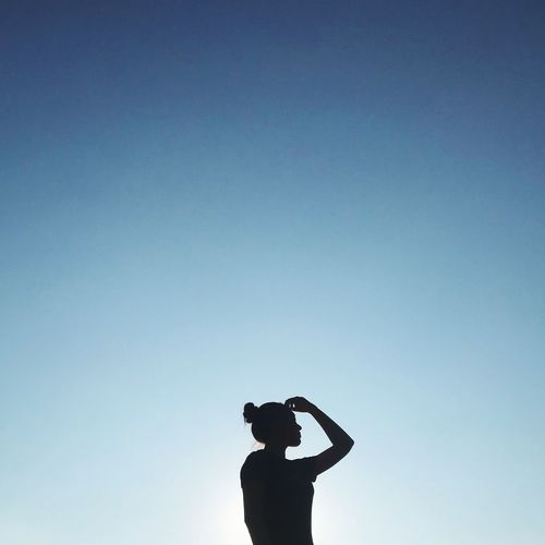 Low angle view of silhouette woman standing against clear blue sky