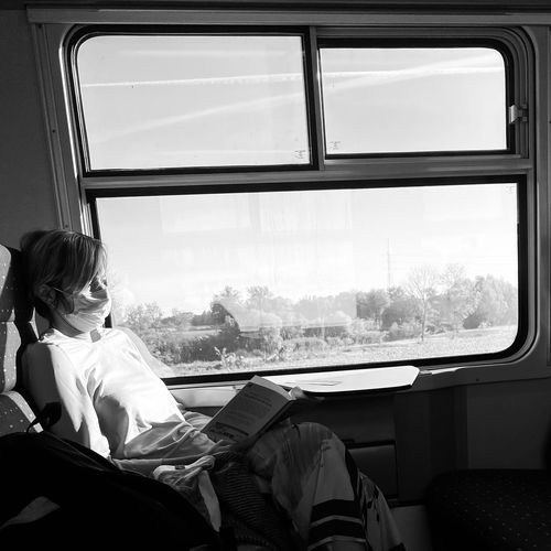 Rear view of woman sitting in train
