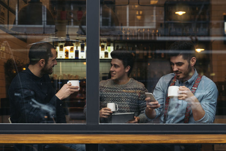 Colleagues talking while sitting in cafe seen through window