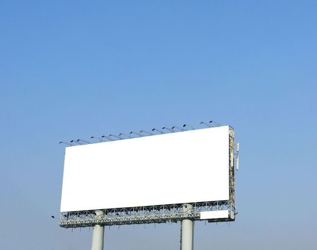 Advertisement Billboard Blank Blue Clear Sky Commercial Sign Communication Copy Space Day Information Lighting Equipment Low Angle View Metal Nature No People Outdoors Sign Sky Sunlight White Color