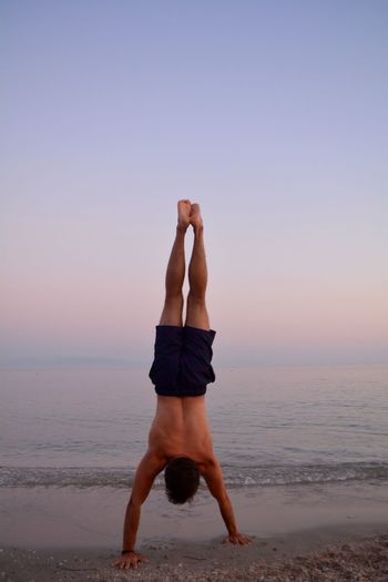 Full length of man doing handstand at beach against sky