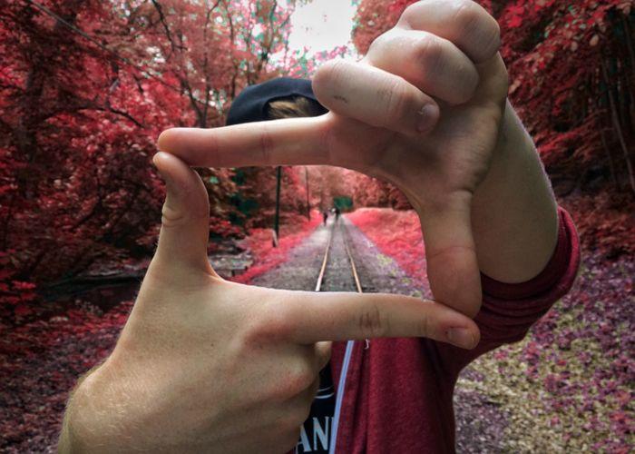 Digital composite image of railroad track seen through man hands