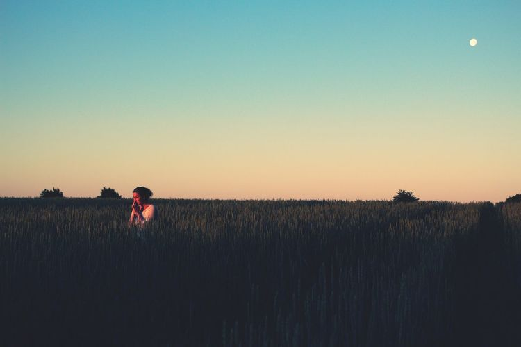 Woman standing at farm against clear blue sky during sunset