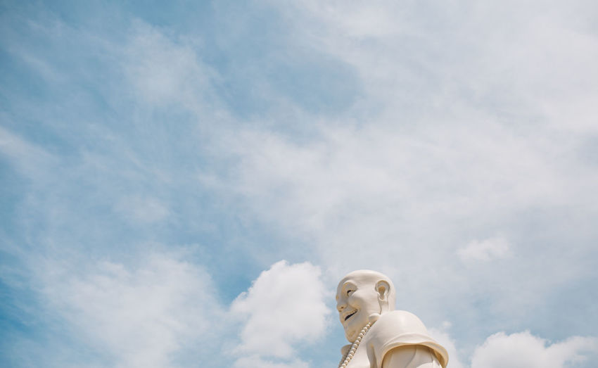 Low angle view of male statue against cloudy sky